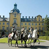 Riders from Bückeburg's Royal Court Riding School against the backdrop of the castle